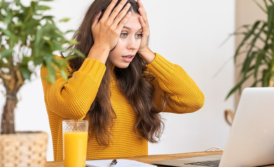 """Email marketer with the """"oh no"""" face spotting a mistake with an email on her computer"""